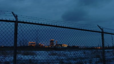 Medium wide angle Esso oil refinery viewed through tall wire mesh fencing as dusk turns to night Montreal Canada