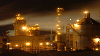 Mid shot Esso oil refinery all lit up at night with streaming clouds from chimneys Montreal Canada