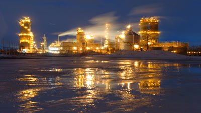 Medium wide angle Esso oil refinery all lit up at night with reflection in melting ice and streaming chimneys Montreal Canada