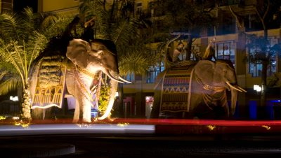 Medium wide angle two floodlit lifesize elephant statues with traffic streaming past and buildings in background with Chinese signs Xinghong China