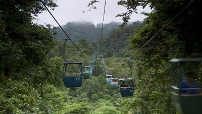 Mid shot cable cars coming directly to and away from camera along wires as they take Chinese tourists up a mountain Wild Elephant Valley China