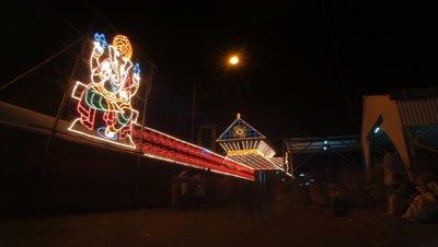 Medium wide angle electric illuminations outside Krishna Temple with visitors streaming past Kerala, India