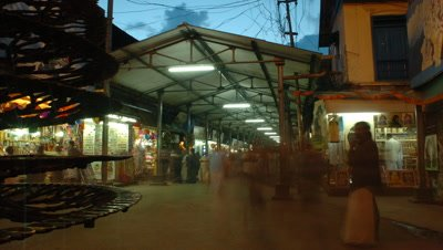Medium wide angle arcade of religious shops leading to temple entrance with visitors streaming passed Kerala, India