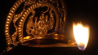 Close up golden figurine depicting Ganesh, sits over incense bowl burning with small flickering flame with black background Kerala, India