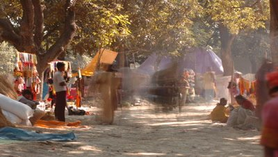 Medium wide angle Informal market stalls amongst trees with people coming and going, Sonpur, Bihar, India