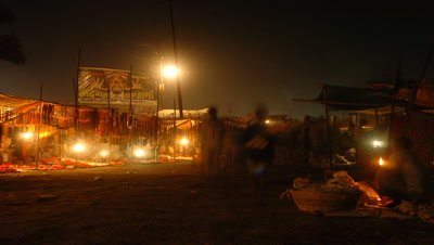 Medium wide angle alley in night market, lantern lit stalls to side, people moving to and from camera, browsing stalls, Sonpur, Bihar, India