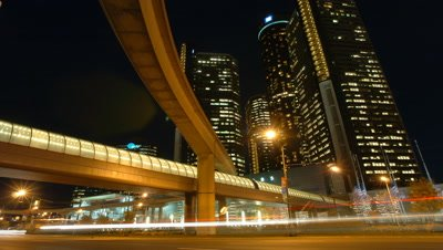Medium wide angle side view of busy traffic with illuminated flyover bridge to General Motors showroom in background, Detroit, USA