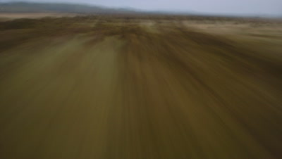 Wide angle view riding on speeding bullet as travel over grasslands and bush