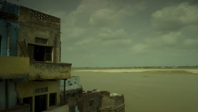 Medium wide angle looking passed buildings across the River Ganges to far bank with boiling clouds racing overhead
