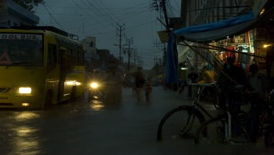 Medium wide angle flooded city street during Monsoon with pedestrians and slow moving traffic