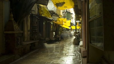 Medium wide angle looking down narrow wet alley, post rain, people streaming through