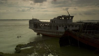 Medium wide angle stormy clouds racing across River Ganges with stranded boats on mud
