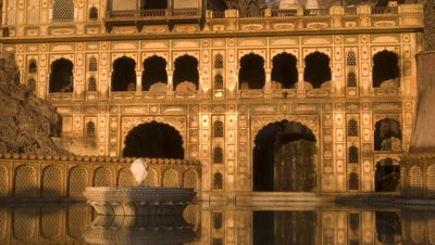 Medium wide angle sun rises on elaborate Rajasthani building faзade featuring typical arches