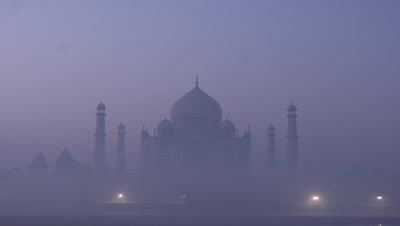 Medium wide angle misty sunrise over Taj Mahal, emerges from darkness to very misty reveal