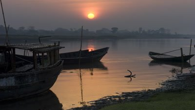 Medium wide angle red sun rises from darkness over f/g moored boats on the River Ganges