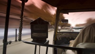 Medium wide angle point of view of passenger in tuk-tuk looking over driver's shoulder to traffic