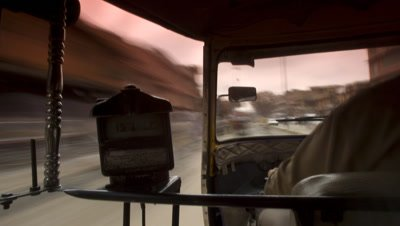 Medium wide angle point of view of taxi passenger in tuk-tuk looking over driver's left shoulder to traffic