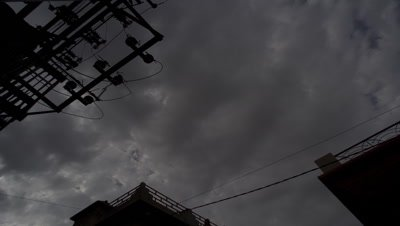 Medium wide angle panning shot looking up at gathering storm clouds through power pylon with architectural detail behind