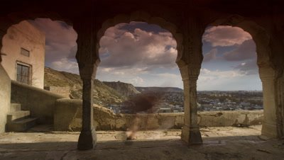 Medium wide angle panning shot over Jaipur city viewed through Galta temple arches with gathering monsoon clouds but no sun glints