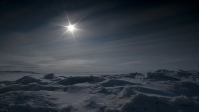 Wide angle dramatic sea ice, moody arctic star sun travelling along the horizon at Grise Fjord