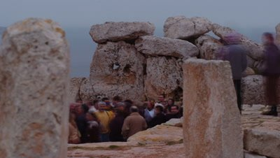 Mid shot crowds of visitors streaming passed standing stones of Megalithic Temple in Malta