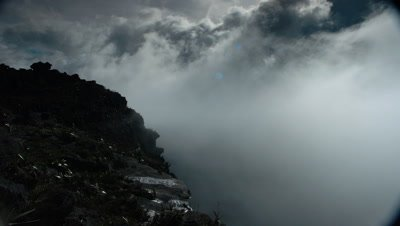 Mid shot dramatic moody boiling clouds over edge of Tepuy, Mt Roraima with wet black rock with mist wiping frame