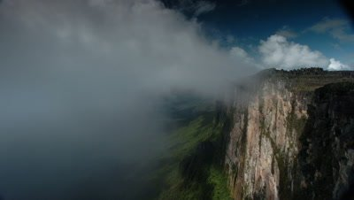 Medium wide angle looking along Mt Roraima cliff face with mist wiping frame to reveal green slopes and landscape below