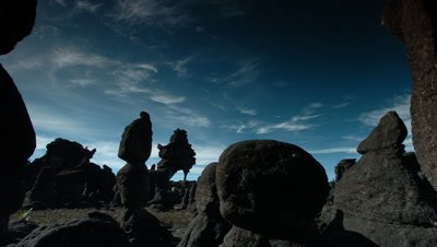 Wide angle rich deep blue sky with wispy white clouds framed by weird black sculptural rock formations on top of Mt Roraima