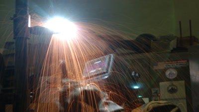 Close up welder in helmet welding a steel plate for Golden Gate Bridge repairs