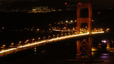 Medium wide angle curve of illuminated Golden Gate Bridge with one tower and fast flowing night traffic and lights of the shoreline