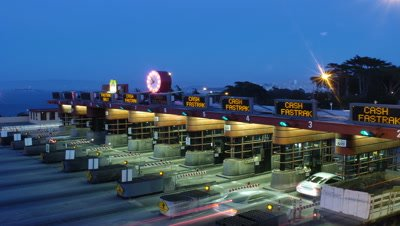 Medium wide angle top shot floodlit toll booths of Golden Gate Bridge with cars stopping to pay as evening becomes night