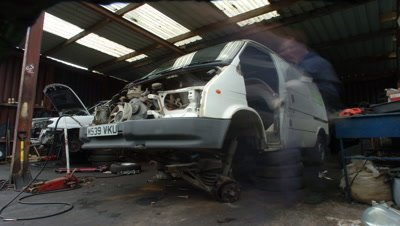 Mid shot white van in open-fronted shed being dismantled for scrap by garage mechanics