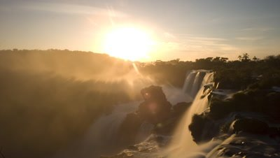 Wide angle sunrise over top of Iguazu Falls with motion blur water flow and spray rising in soft morning light