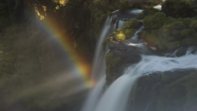Mid shot looking down over Iguazu Falls with spray rainbow and motion blur