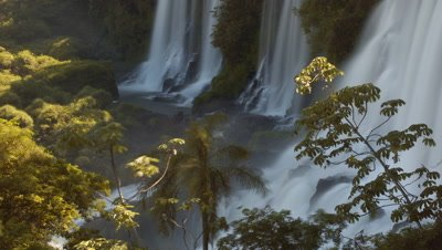 Mid shot base of Iguazu Falls framed with vegetation - very short shot