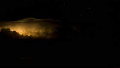 Medium wide angle black sky with golden cloud constantly illuminated by blanket lightning