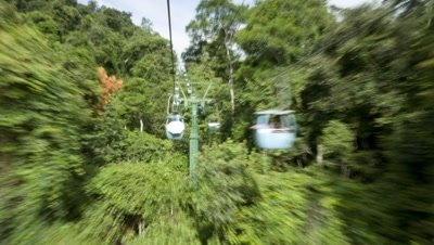 Medium wide angle point of view from cable cars travelling forward along wires as taking Chinese tourists up a mountain