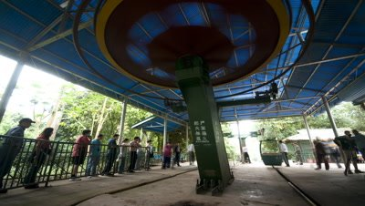 Medium wide angle cable car station with people queuing up and getting into cars