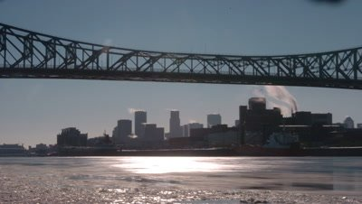 Medium wide angle Montreal city skyline viewed across an icy St Lawrence River and under bridge span