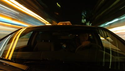 Mid shot car with bonnet mounted camera facing driver as drive through city streets illuminated with Xmas fairy lights