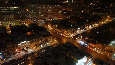 Wide angle top shot busy city intersection with constant traffic and featuring illuminated city buildings