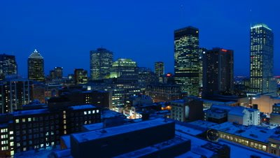 Medium wide angle high rise buildings in Montreal city centre as blue eve becomes black night