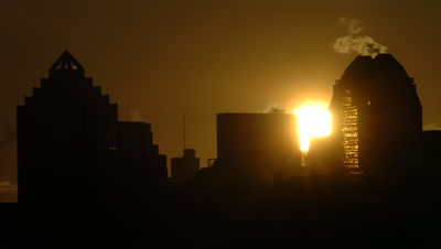 Mid shot high rise buildings in Montreal city centre with streaming ventilation shafts as sun sets