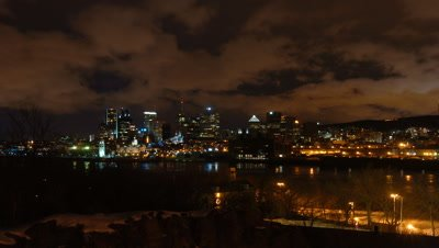 Wide angle Montreal city skyline viewed from high point across St Lawrence River with night clouds racing to camera