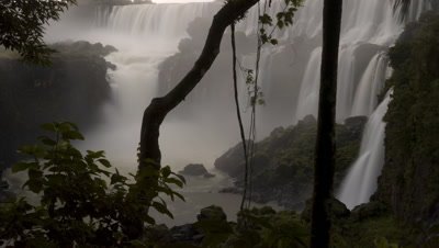 Mid shot base of Iguazu Falls framed with lush vegetation with motion blur water and rising spray