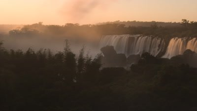 Medium wide angle view of falls over vegetation with spray rising above trees and light lifts as sun rises