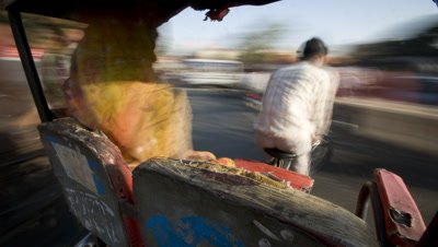 Medium wide angle looking over lady passenger in saris' shoulder in bicycle rickshaw as driver pedals his way through busy traffic