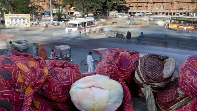 Medium wide angle panning shot from busy chaotic intersection to single traffic flow with arcade of shops behind and turban stall