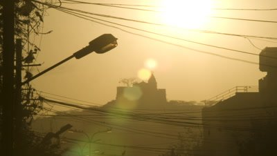 Medium wide angle sun and flare rises over silhouetted Hindu temple with passing people and mesh of electricity cables and streetlights in foreground
