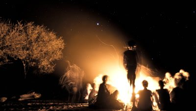 Wide angle tribal people San bushmen gathered around a campfire in the bush with big sky and stars